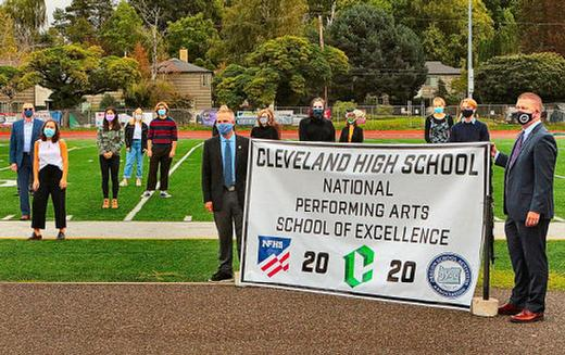At the CHS athletic field, officials from the National Federation of State High School Associations present the banner proclaiming Cleveland High School this year�s national 2020 NFHS �Performing Arts School of Excellence�.