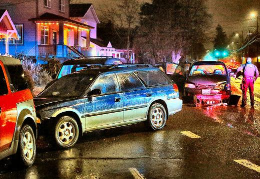 An East Precinct officer examined the damage after a head-on crash in the rain on Woodstock Boulevard�s �notorious curve� at S.E. 69th.