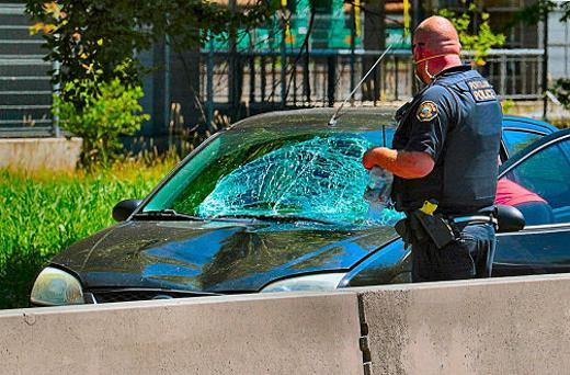 A Central Precinct officer examined the damaged northbound car which struck a pedestrian who was crossing S.E. McLoughlin Boulevard � by clambering over the high median �Jersey Barrier� near the Bybee Bridge.