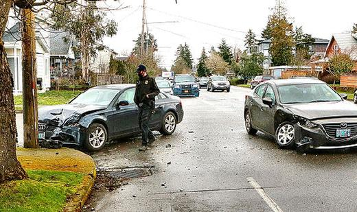 An East Precinct officer examined the two wrecked cars, after they collided on S.E. Woodstock Boulevard.